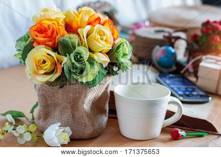 roses and a cup of coffee on the desk.