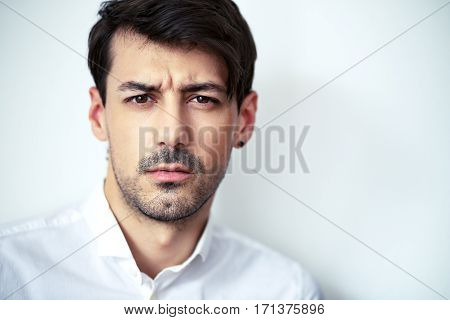 close up portrait of young serious handsome man wearing white shirt looking with suspicion at camera posing next to color background in photostudio