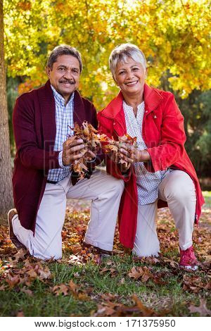 Portrait of mature couple holding autumn leaves while kneeling on field at park