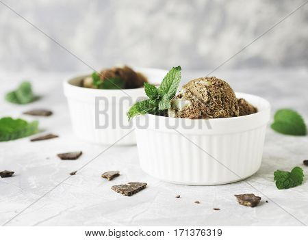 Chocolate Mint Ice Cream In White Bowls With Pieces Of Chocolate And Mint Leaves On A Marble Table