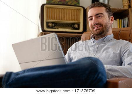 Man working at home using his laptop and wi-fi internet connection