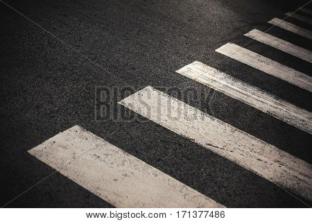 Abstract of a crosswalk, simple closeup view on asphalt.