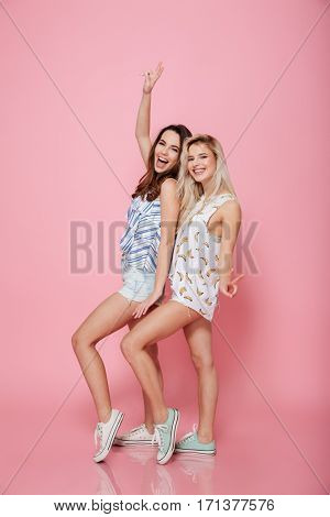 Full length of two cheerful young women showing peace sign and having fun over pink background