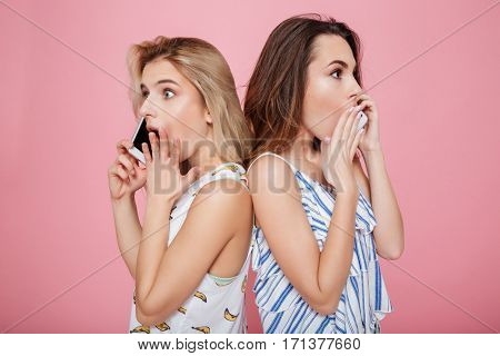 Two shocked surprised young women standing and talking on cell phones over pink background