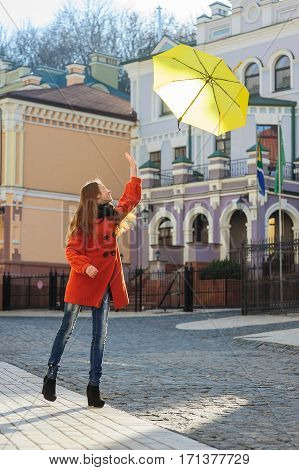 young woman with a yellow umbrella jumping outdoors.