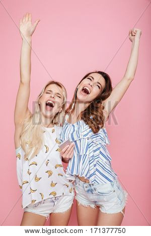 Two happy young women listening to music from smartphone and singing over pink background