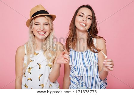 Two smiling cute girls standing and chewing bubble gum over pink background