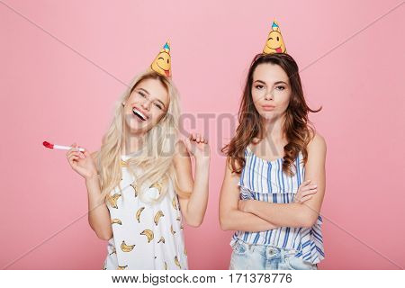 Sad and happy young women in hats celebrating birthday over pink background