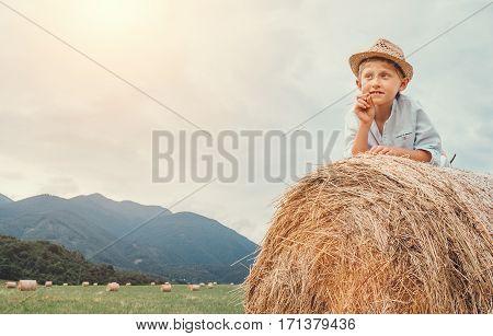 Boy in sraw hat lying on hay roll