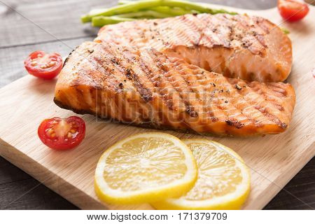 Grilled Salmon And Lemon, Asparagus, Tomato On The Wooden Table