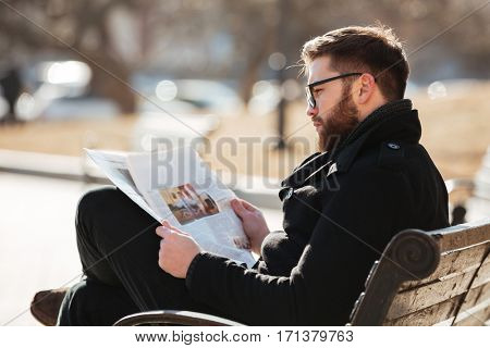 Handsome bearded young man in glasses sitting and reading newspaper in the city
