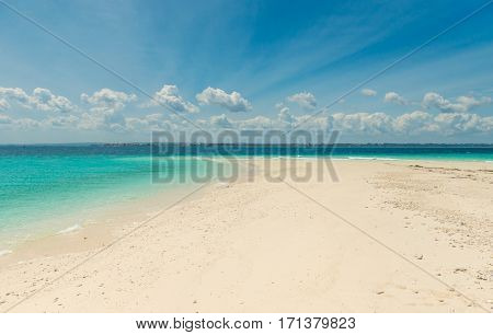 sandbank with transparent turquoise water and blue sky on the background