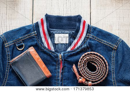 jackets of blue jeans and wallet on the wooden floor.