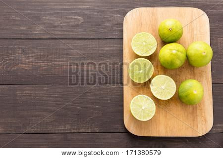Fresh Limes On Cutting Board On Wooden Background