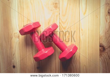 Pair of red 1 kg dumbbells on wood vintage tone. pink dumbbells. dumbbells on table. dumbbells on wooden background. dumbbells fitness concept. dumbbells closeup.