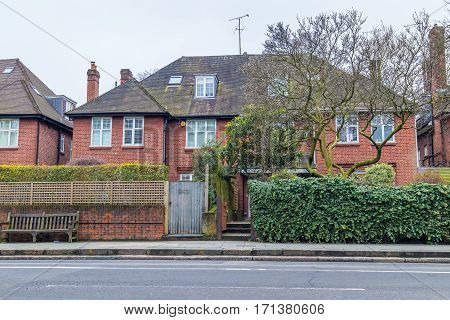 Typical detached house in London suburbs with a large garden in front. Made of orange clay bricks