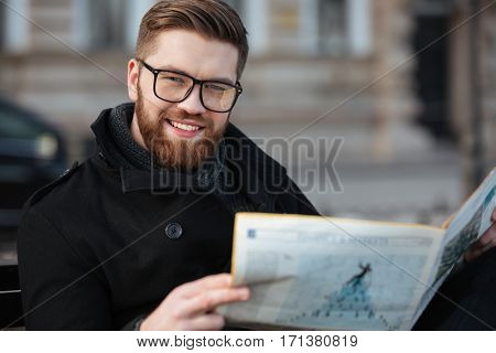 Portrait of cheerful bearded young man in glasses reading newspaper outdoors