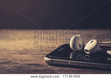 Earphone and phone media portable on dark tone. Earphone and smartphone on wood table. Earphone and phone depth of field. Earphone or earphones on white background.the white earphones for using digital music or smart phone.
