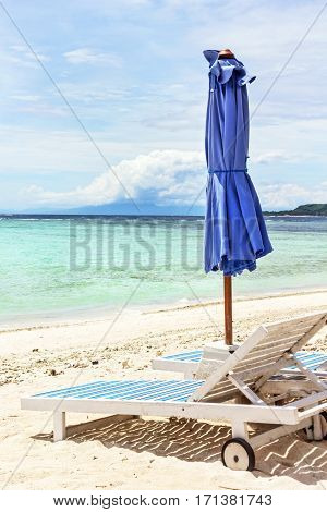 Loungers on white sand by ocean at sunny day