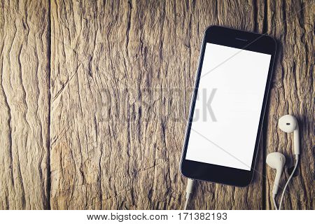 Smartphone with headphones on wooden table. Smartphone white screen. Smartphone on wood. black color Smartphone. Smartphone mobile. Smartphone blank screen. Smartphone and earphone.