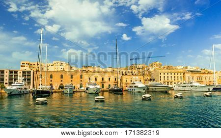 yachts anchored in Valletta bay with yellow city walls on the background, Malta