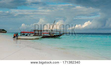 beautiful landscape with diving instructors putting equipment in touristic boat on Zanzibar shore