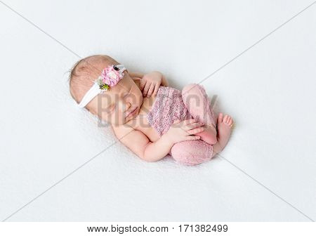 Adorable baby resting in a funny pose, dressed in a pink laced costume