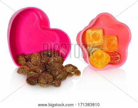 Multi colored kitchen molds with raisins and candy. Box closed in the shape of heart and star. Containers in the colors pink red. Cookie cutters on a white background with slight reflection.