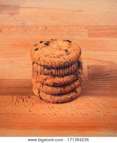 Home made chocolate cookies on wooden background. Crispy chip biscuits with chocolate and hazelnuts. Delicious fresh chocolate chip cookies.