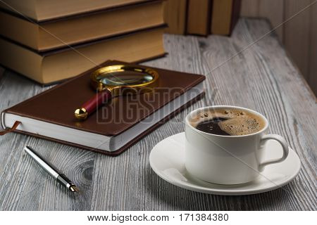 Closed Notebook With A Fountain Pen On Rustic Table. Magnifying Glass On A Notepad.