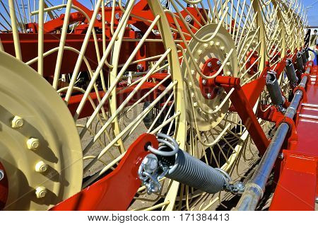 The wheels and springs of a new side delivery wheel rake for creating windrows in haying forage