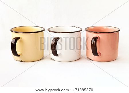Three old retro metal tea cups in a row isolated. Some yellow white rose pastel color beautiful ceramic mugs for coffee
