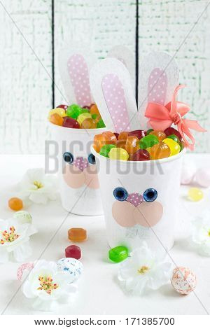 Paper cups in the form of funny Easter Bunny with candy. Homemade applique on paper cups. The idea for children gifts. DIY concept for the celebration of Easter. Vertical selective focus