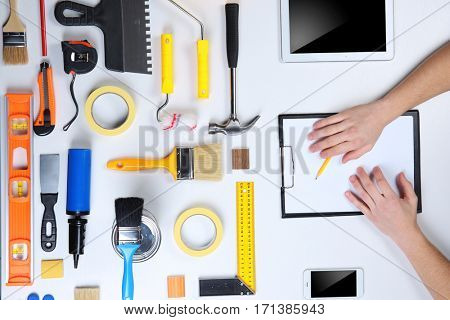 Decorator's hands with pencil and clipboard. Color swatches and tools on work table