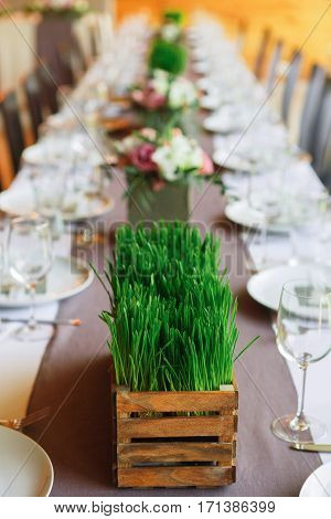 Beautifully organized event - served festive table ready for guests, decorated with grass and flowers. Event in restaurant outdoors. Banquet, wedding decor, celebration. Vertical orientation