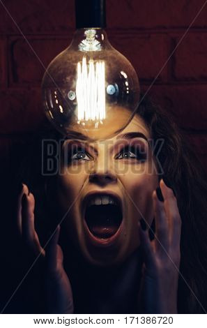 Woman in the darkness screaming on the lamp. Emotional photo.