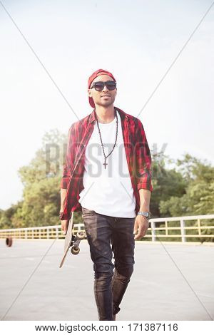Picture of young dark skinned boy wearing sunglasses and cap holding skateboard. Against the nature background.