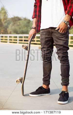 Picture of young dark skinned man holding the skateboard. Against the nature background.