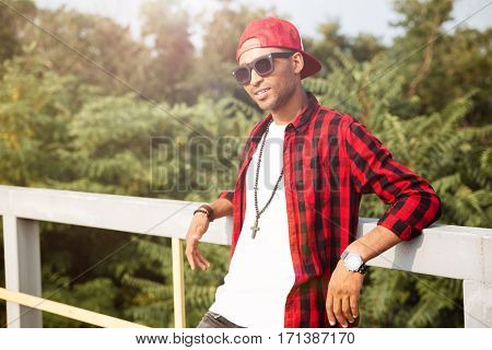 Photo of young attractive dark skinned guy wearing sunglasses against nature background