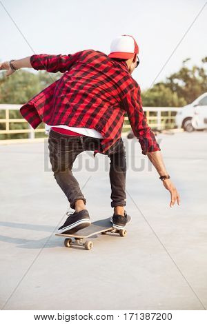 Photo of young dark skinned guy skateboarding. Against the nature background.