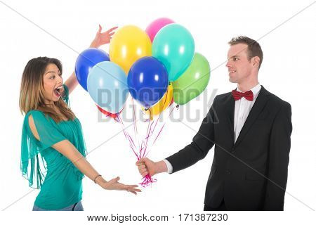 Young man with a bunch of colorful balloons making his girl friend happy isolated over white background