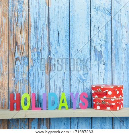 Blue wooden background for holidays with suitcases