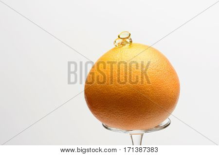 Grapefruit With Capsule On Wineglass Isolated On White Background
