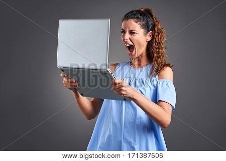 A beautiful young woman standing and screaming while grabbing a laptop with both hands.
