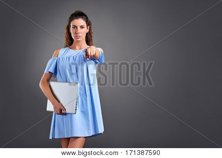 A serious beautiful young woman pointing in to the camera while holding a laptop in her hands.