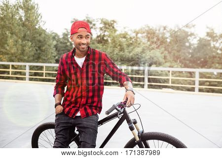 Picture of cheerful dark skinned man wearing cap standing near his bicycle. Against nature background.