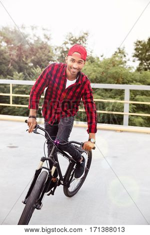 Photo of happy dark skinned man wearing cap sitting on his bicycle. Against nature background.