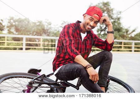 Photo of happy dark skinned boy wearing cap sitting on his bicycle. Against nature background. Looking at the camera.