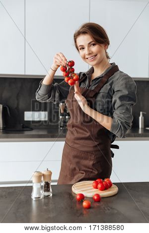 Photo of young pretty woman standing in kitchen holding tomatoes in hands.