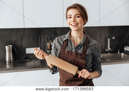 Picture of young beautiful woman standing in kitchen holding rolling pin in hands. Looking at camera.